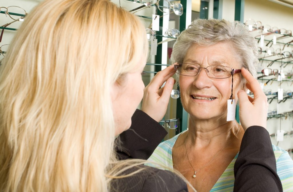 Optician puts glasses with price tag attached on smiling woman in store
