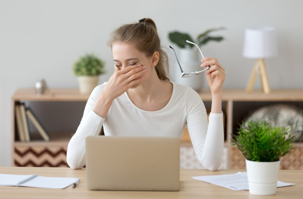 Woman holding glasses and rubbing tired eyes in front of laptop