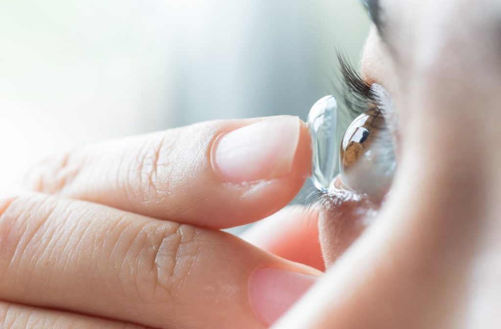 A woman placing her multifocal contact lens on her eye