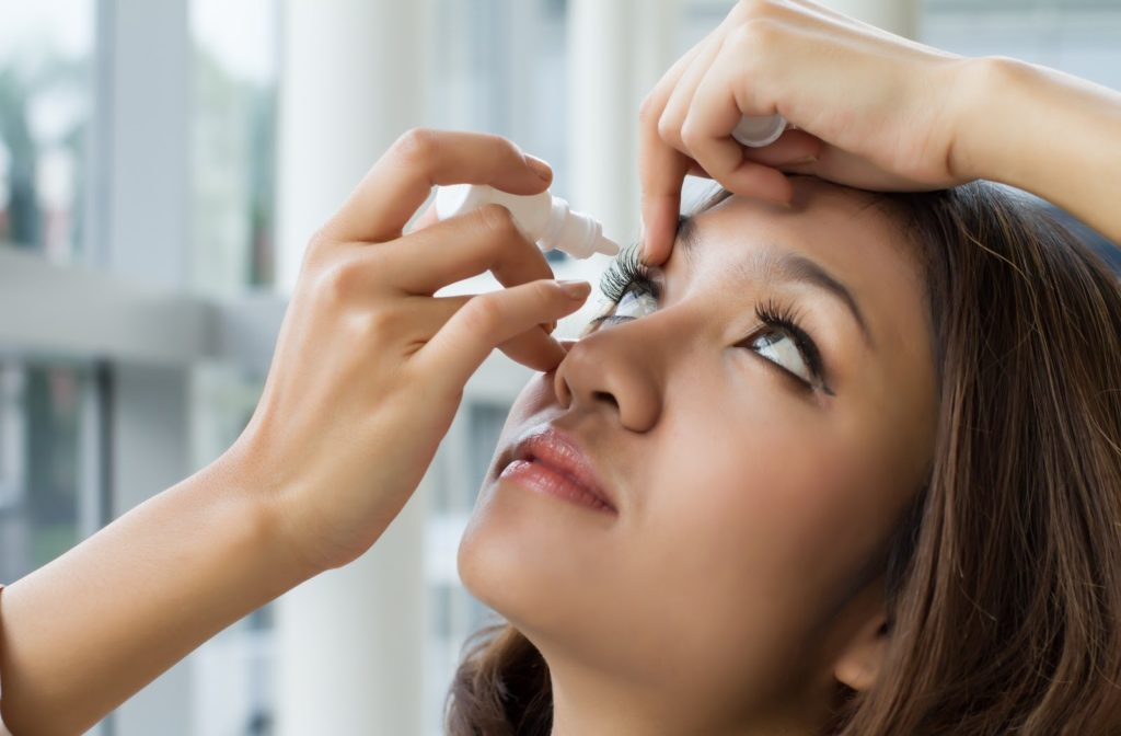 Young woman applying eye drops by opening her eyelid with one hand and using her other hand to squeeze drops into her eye