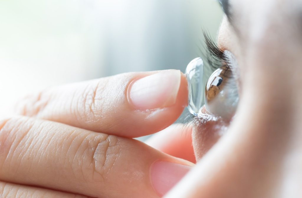Close up of woman putting contact lens into her eye