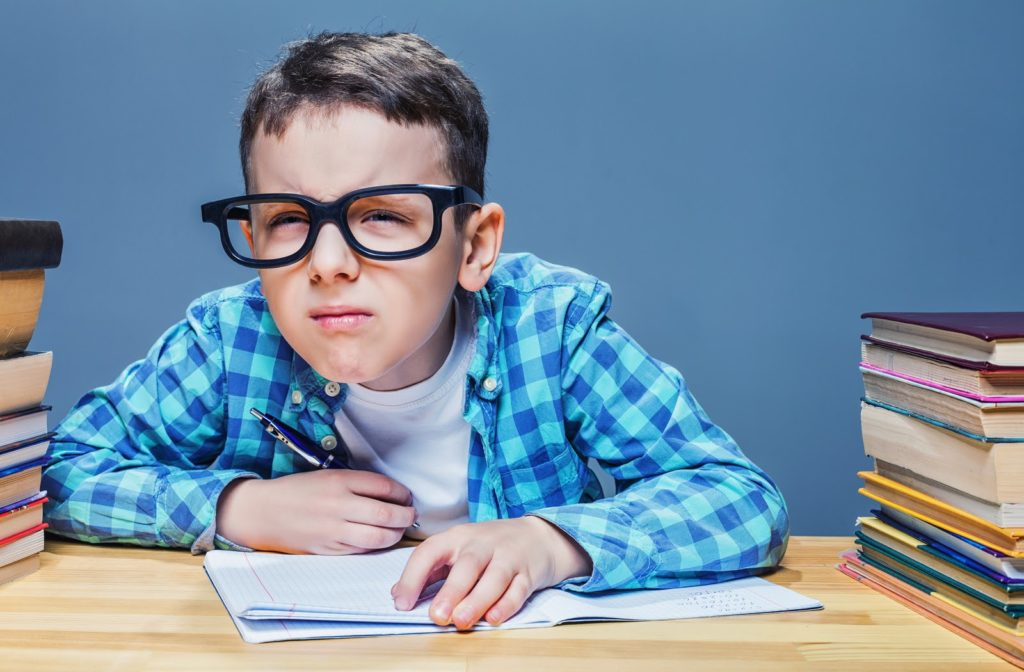 Young boy squinting to be able to see board as he takes notes in his notebook